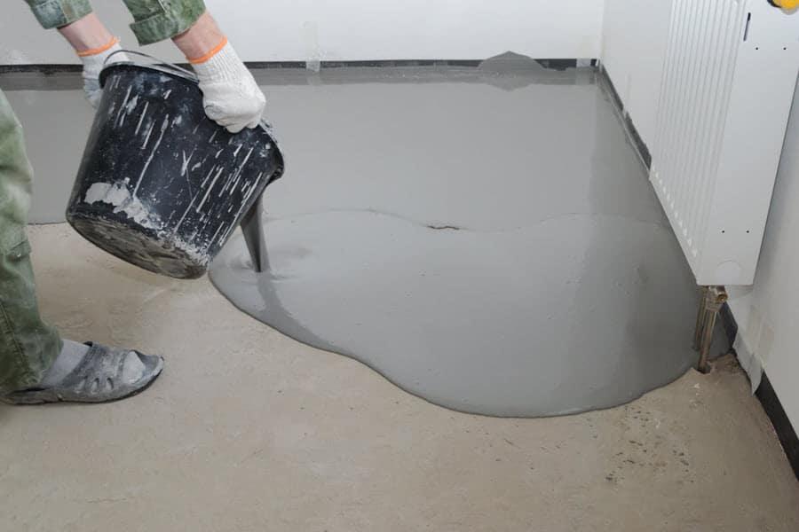 Person applying grey epoxy paint to workshop floor.